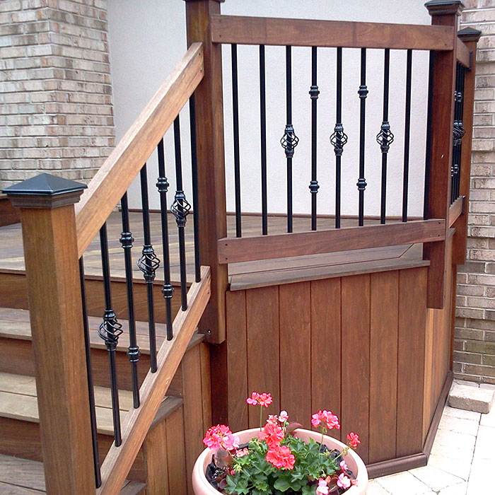 a wood deck with round balusters adorned with baluster collars and baskets