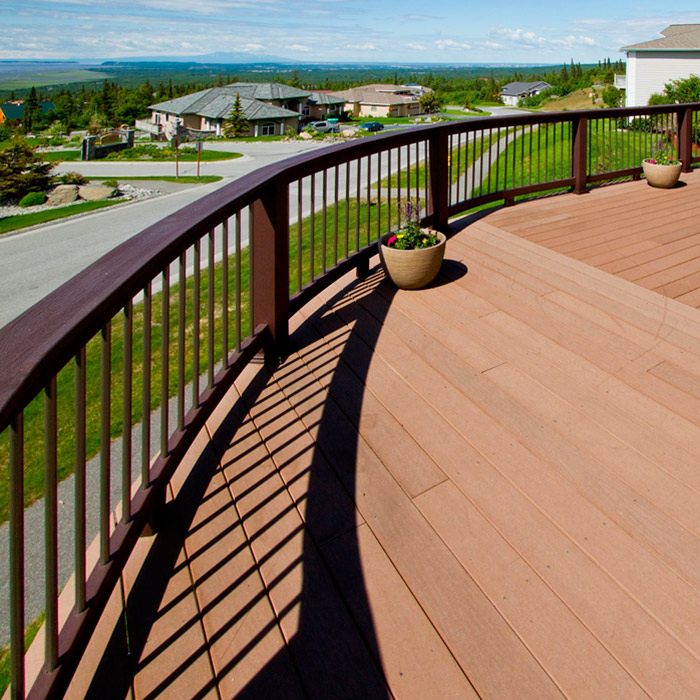 a curved deck railing with round balusters