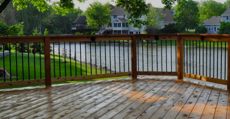 a cedar deck with wood railings and Round Metal Balusters overlooking a lake
