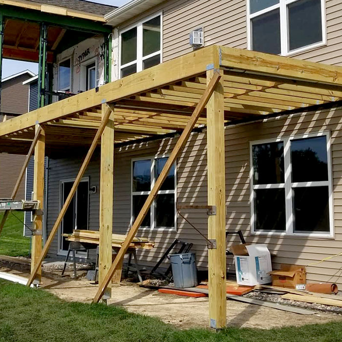 the beginning of a deck with framing and posts in place