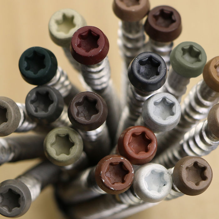 a close up of deck screws with colored torx drive heads