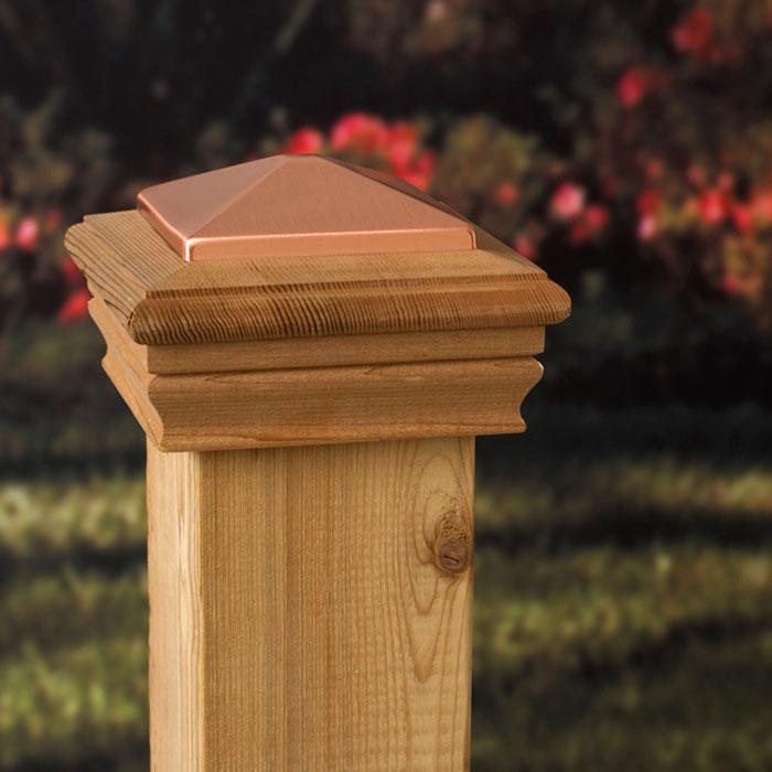 a deckorators wood and copper post cap on a cedar post