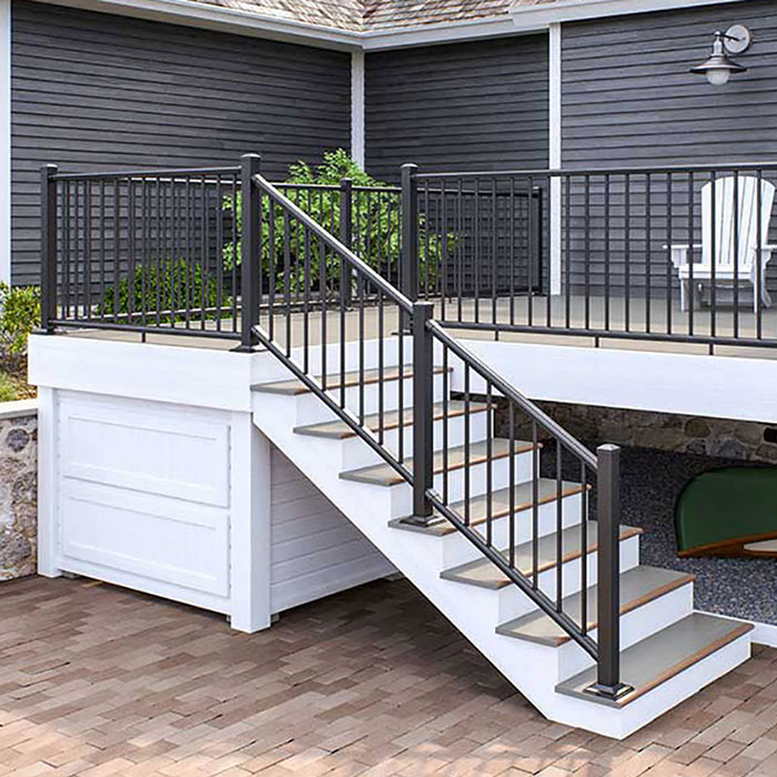 Backyard deck with white Adirondack chairs, enclosed with Deckorators ALX Classic Railing in Black and stairs lead down to paver patio