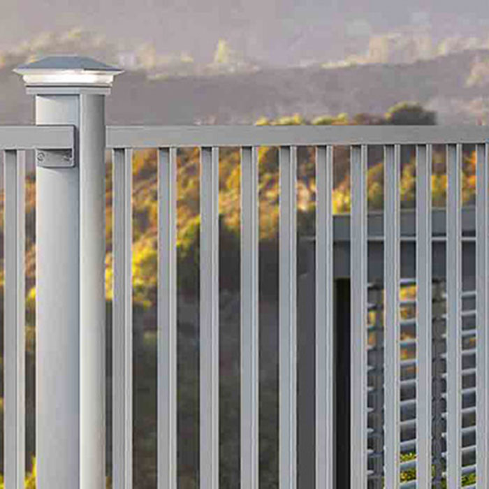 Silver aluminum railing with matching caps in front of a hill with changing leaf colors
