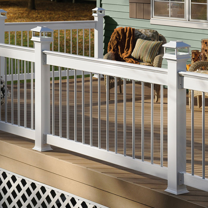 Deckorators ALX Pro Railing in White with Cap Rail Kit, White Classic Round Balusters, and White Solar Post Caps by Deckorators surrounds a tan deck on a green house with wicker furniture and potted flowering plants