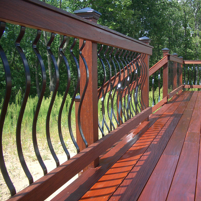 Deckorators Baroque Architectural Face-Mount Aluminum Balusters installed on wood rails.
