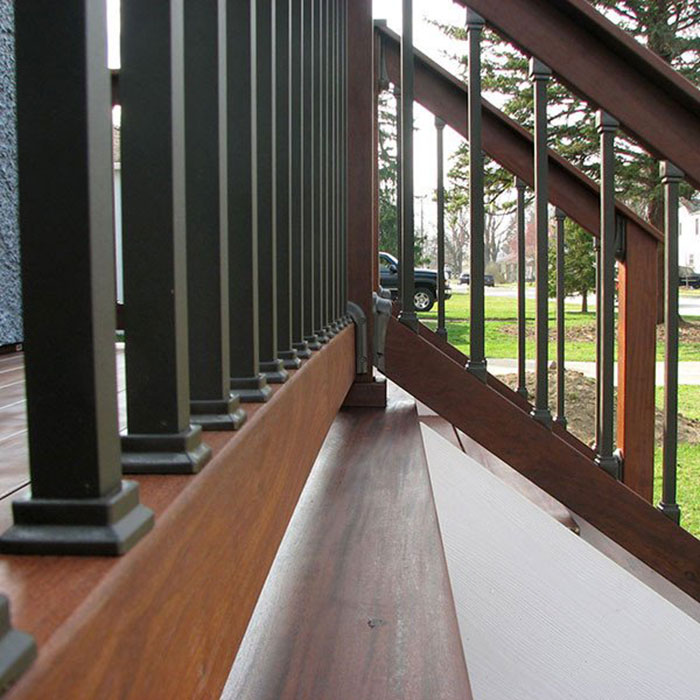 Close up of Deckorators Square Estate Baluster Connectors installed on a stained wood railing
