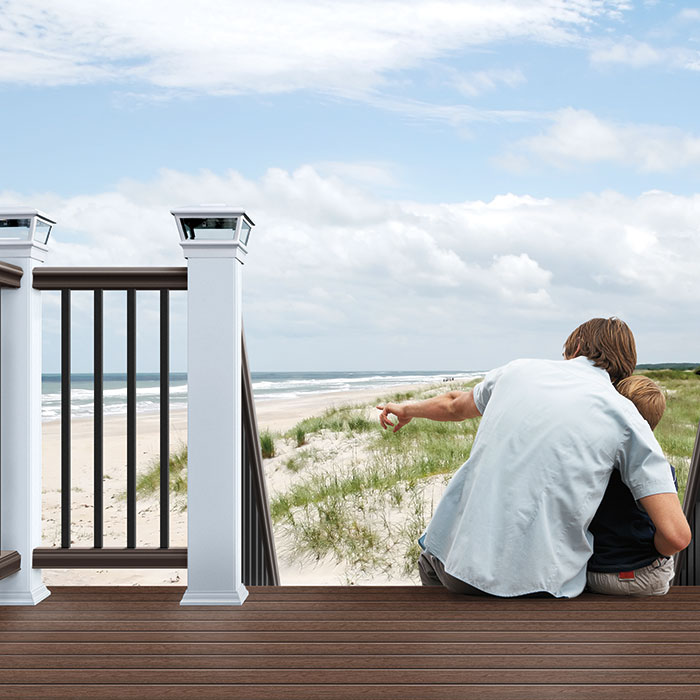 A man and boy sit on composite deck stairs leading down to a beach, the deck railing features white Deckorators post sleeves with Solar VersaCaps