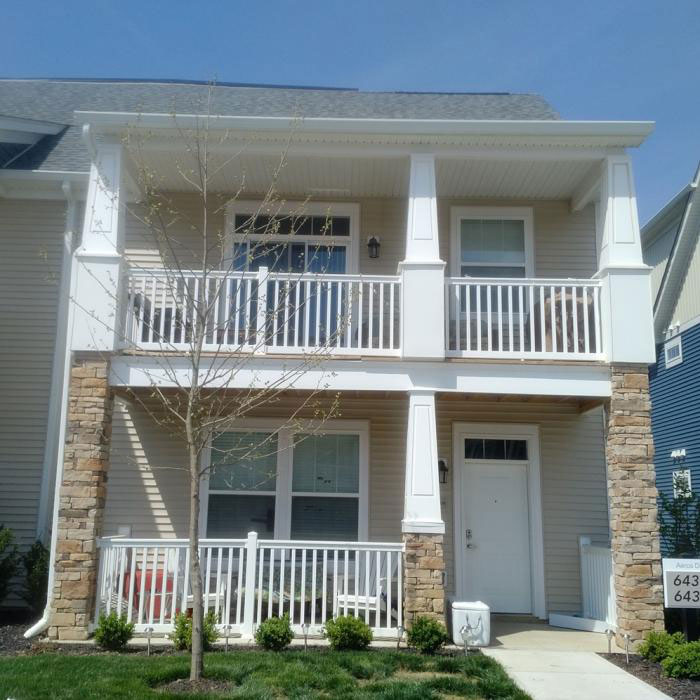 A second-floor balcony features Durables Brighton t-top white vinyl rail with rectangular balusters