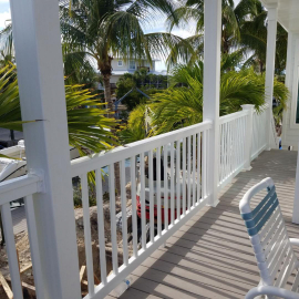 An elevated patio wrapped with Durables Brighton Vinyl Railing in white.