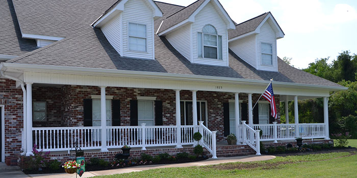 a beatiful house with a porch made of Durables Vynal railing and an amaerican flag