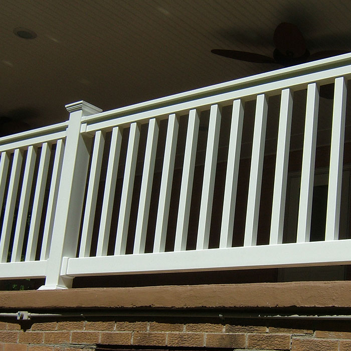 Durables Harrington railing in white on a porch of a brick house