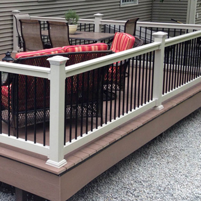 Durables Kirklees t-top vinyl rail in tan with black round aluminum balusters is installed on a low backyard deck with a dining table and lounge set