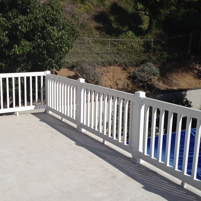 Poolside patio featuring white Durables Manchester Premium Vinyl Railing with square balusters