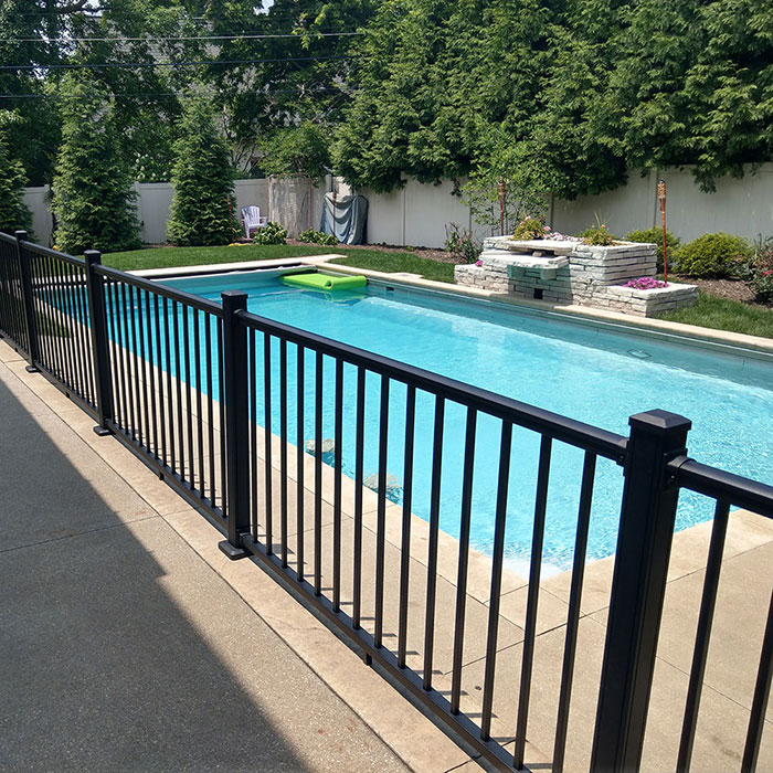 Sterling black aluminum railing surrounding a large backyard pool
