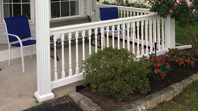 Durables Ashington Vinyl Railing in white on front porch surrounded by flowers and blue chairs