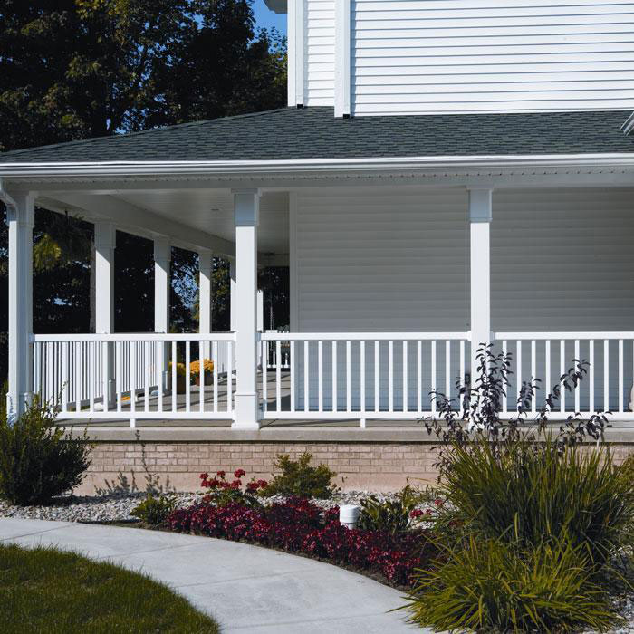 A wraparound porch on a white house features Durables Waltham white vinyl rail with rectangular balusters
