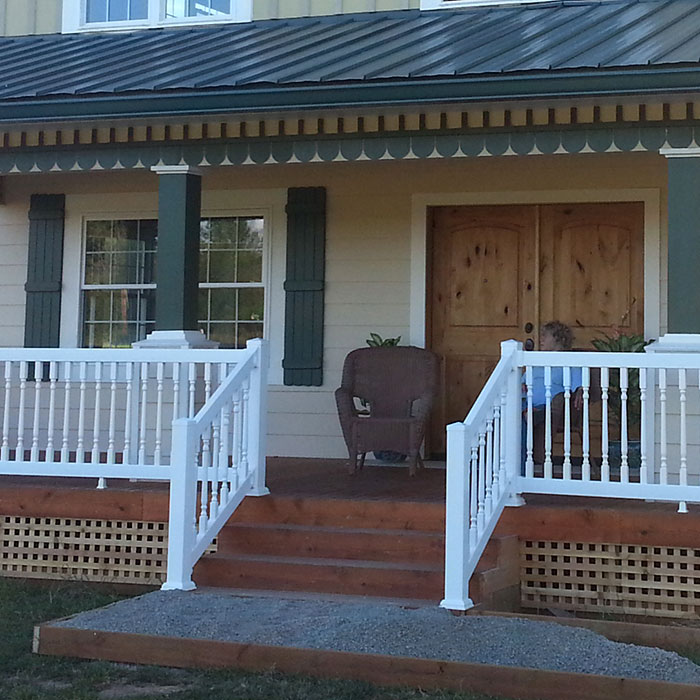 Durables premium Westport vinyl railing with standard top rail and colonial style balusters is installed on a front porch and stairway, featuring 4 inch posts