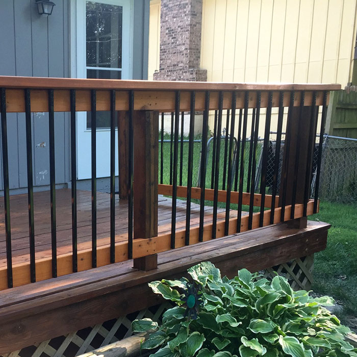 A cedar deck railing featuring Fortress Vintage Series Face-Mount Balusters