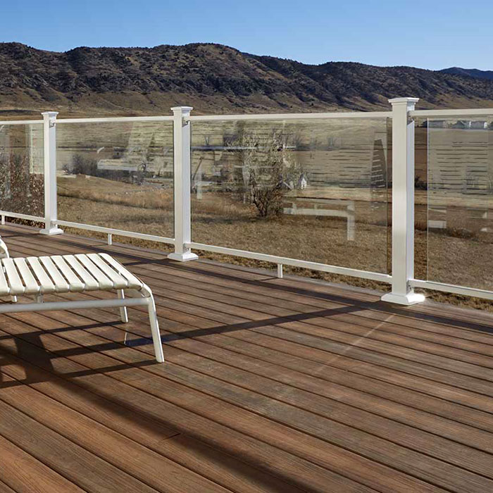 An uninterrupted view from a deck featuring lounge chairs and gloss white Frotress AL13 Full Panel Glass Railing