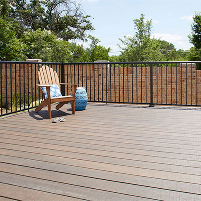 a deck with Fortress AL13 Home Railing in Textured Black with pation furnature on a sunny day