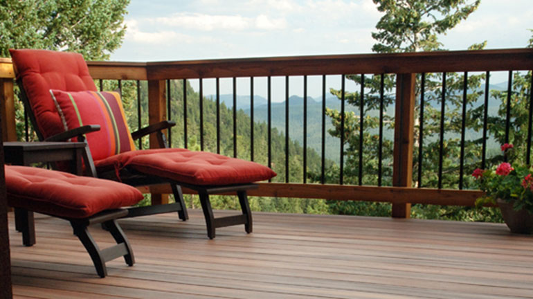 a mountain wood deck featuring Fortress Round Iron Balusters and red lounge chairs