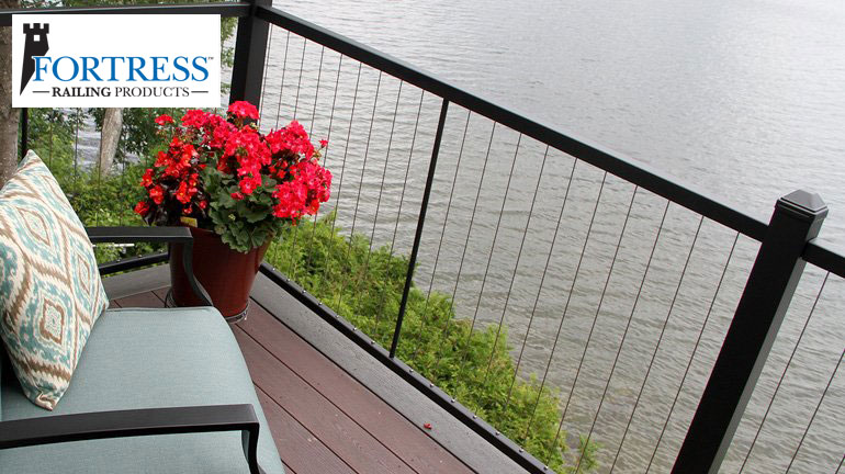 A blue-cushioned chair and potted red flower sit on a 2-tone deck overlooking the water, the deck has Fortress Vertical Cable Railing installed in Black Sand finish