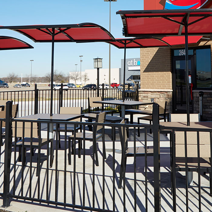 A restaurant patio with Fortress FE26 Iron Commercial railing around patio filled with tables, chairs, and umbrellas