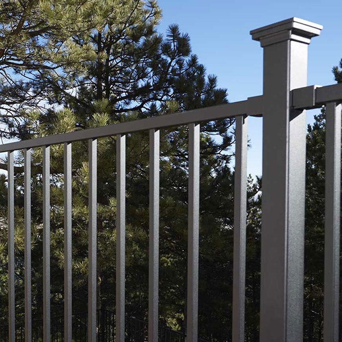 Fortress FE26 Iron Panel Railing system on a composite deck with tree tops in the distance