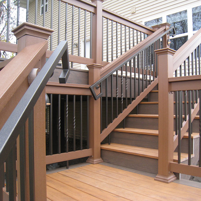 A brown composite deck and railing is equipped with Fortress Square Handrail and Handrail Returns in Antique Bronze
