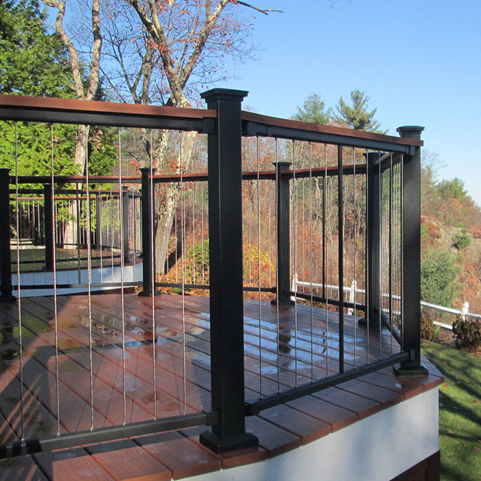 Fortress Fe26 Vertical Cable Railing is installed on an angular deck overlooking a wooded landscape, the deck railing features Black Sand posts and rails, plus utilizes a deck board drink rail