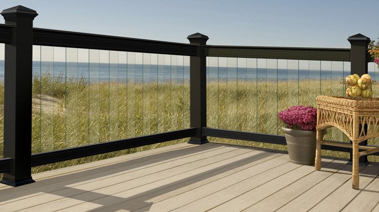 A pink flowerpot and wicker chair sit on a seaside deck which features black Deckorators Aluminum ALX Pro Railing with Frontier Glass Balusters