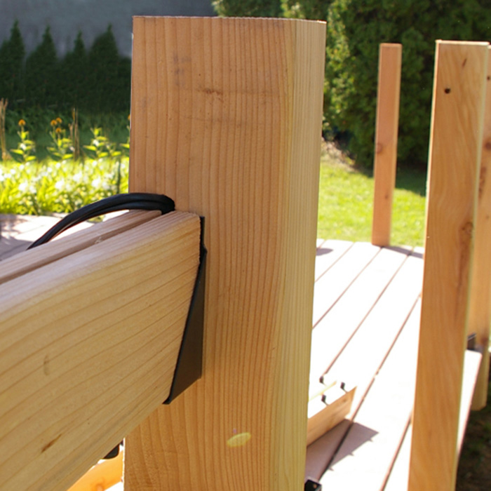 a wood deck rail with a 2x4 that has a channel drilled out for wires