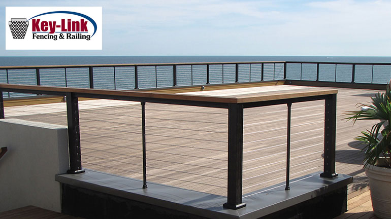 An expansive oceanside deck showcases KeyLink horizontal cable railing with rails and posts in Black Fine Texture and a wooden drink rail to coordinate with the deck surface