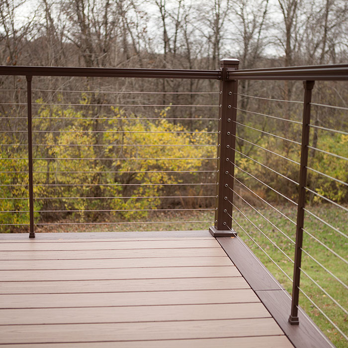 Fall foliage is visible from a composite deck featuring KeyLink Horizontal Cable Railing in Bronze