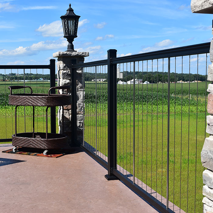 Keylink Cable RAiling on a cement patio with a beverage cart and a view of a farm field