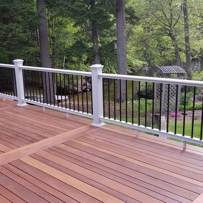 A deck with with railing and Deckorators Classic Round Aluminum Balusters in black