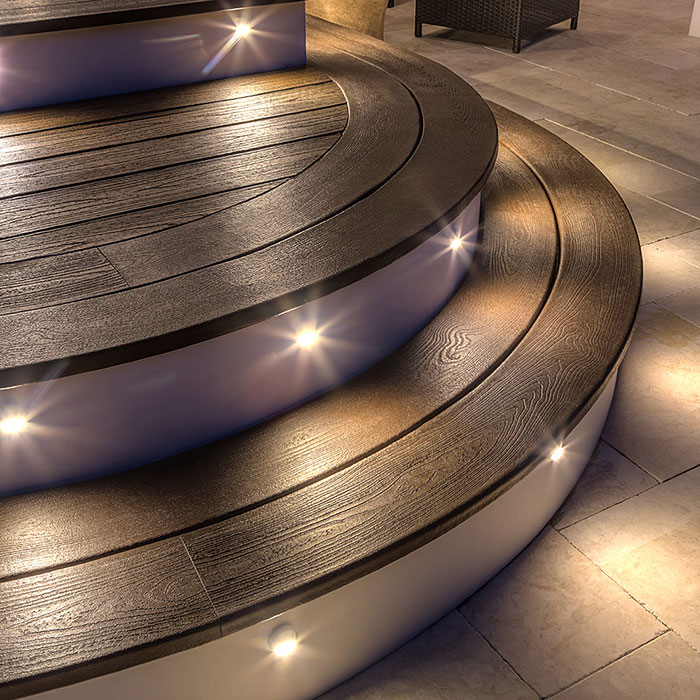 Trex Outdoor Lighting Deck Lighting riser lights on curved steps with Transcend deck in Spiced Rum decking