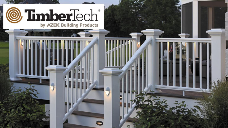 A tan composite deck attached to a purple house with white trim has AZEK Premier Rail in white installed around the perimeter, including Pyramid Post Caps