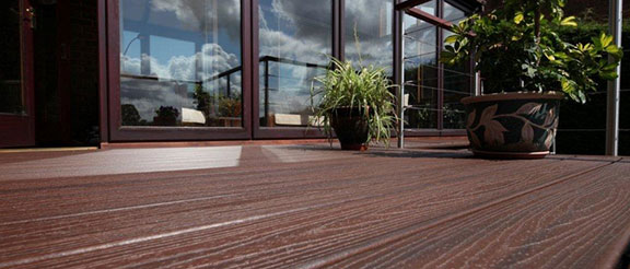 planters sitting on Trex deck with Transcend Decking in spiced rum and glass doors with the sky in the reflection