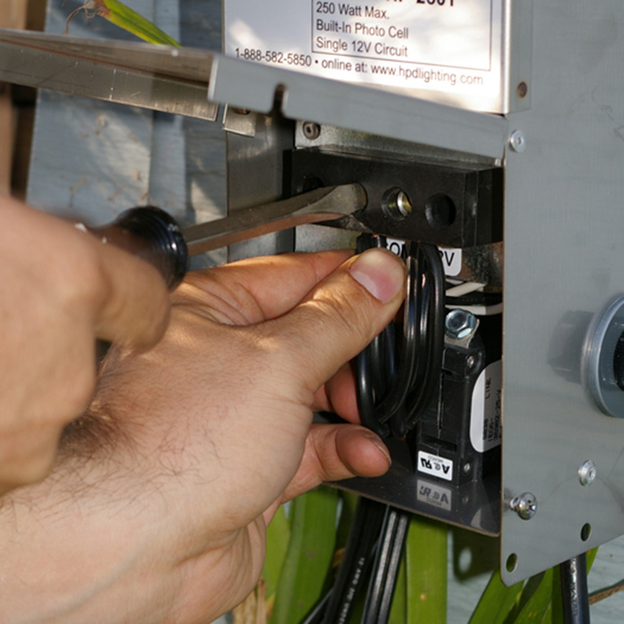 Close up of inside of deck lighting transformer with person using a screwdriver to troubleshoot the unit