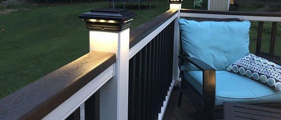 Solar Post Cap Light for Trex Transcend Post Sleeves by Ultra Bright on a Trex Railing with a comfy outdoor chair