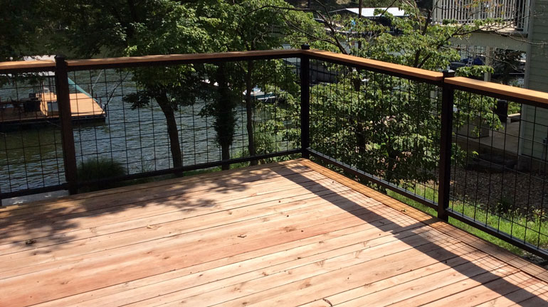 Wild Hog installed with Westbury Veranda rail on a second story deck looking out on a lake.