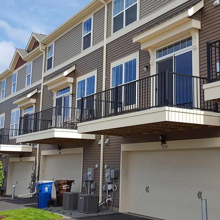 Westbury Aluminum Railing System installed on townhouse balconies above garage doors