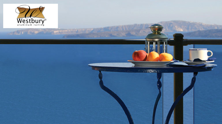 Westbury Veranda Glass Railing next to a table holding peaches and a cup of coffee overlooking a water view
