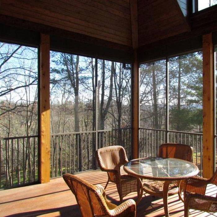 Screened-in porch with wicker dining set overlooks a wooded yard, between 8x8 cedar framing is Westbury ScreenRail in Bronze Fine Texture finish