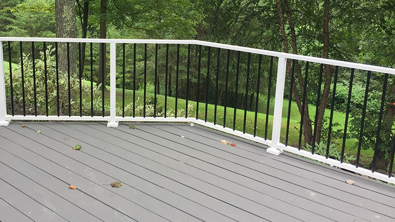A backyard deck with Westbury Tuscany Aluminum Railing in White Fine Texture with contrasting Black Fine Texture Balusters