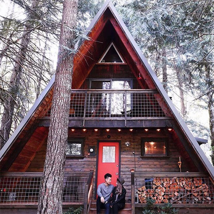 a trendy couple sitting ot the deck of their A-frame cabin with Wild Hog Railing