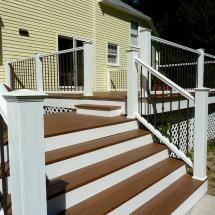 Deckorators CXT Colonial Railing in White with Classic Aluminum Balusters in Bronze. Also features Deckorators collar accessories in Bronze and CXT Stylepoint Post Caps in White.