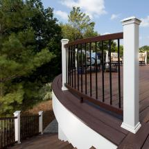 Custom-curved Trex Transcend Rails in Vintage Lantern with Charcoal Black Aluminum Balusters and Classic White Posts and LED Post Cap Lights.